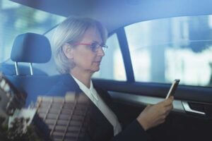 Female business traveller checking her phone a taxi